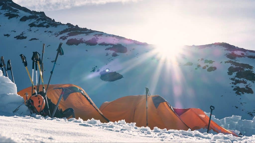 three yellow and red dome tents on snow capped mountain