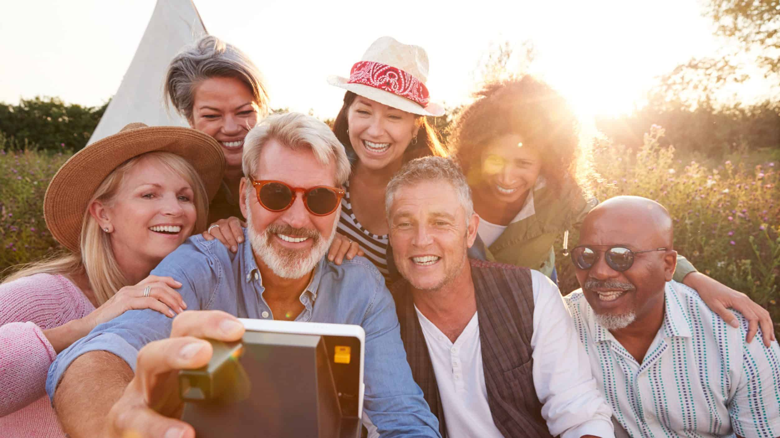 Group Of Mature Friends Posing For Selfie At Outdoor Campsite