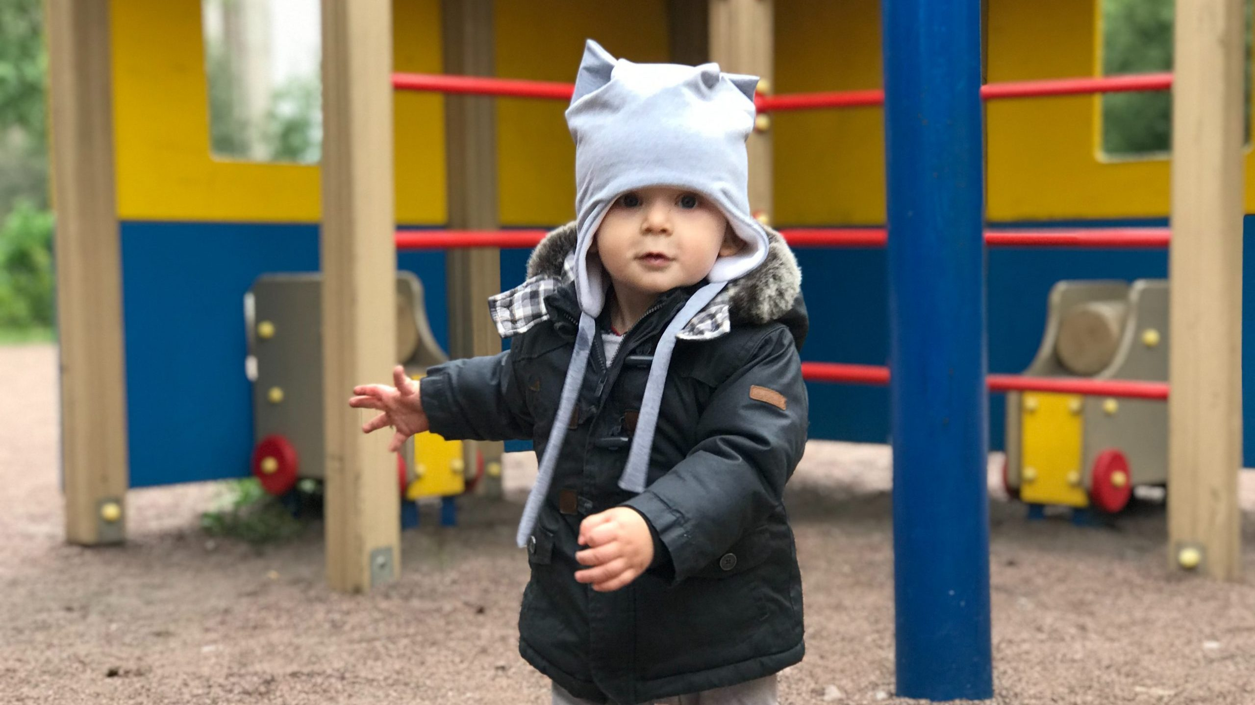 child in black jacket and white cap standing near yellow blue and red playground during daytime